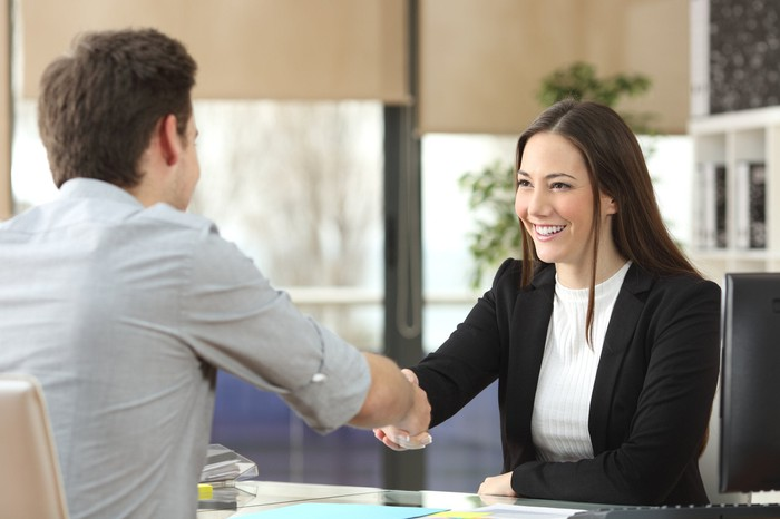Well-dressed young woman shakes hand of a man over a desk.