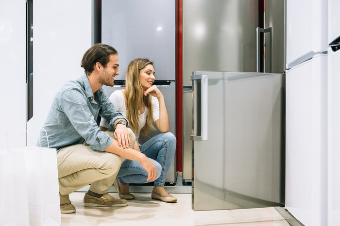 A couple shopping for appliances checks out the lower half of a refrigerator.