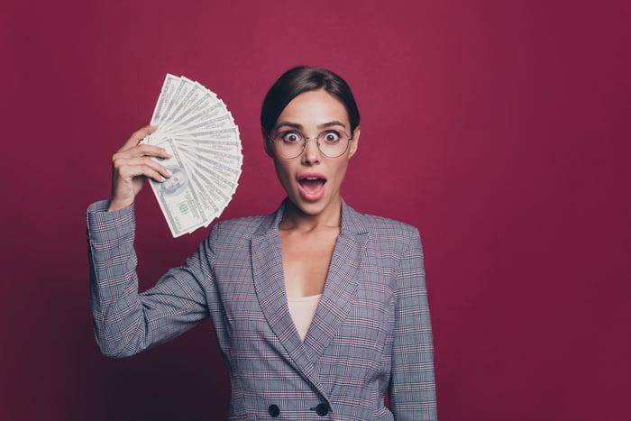 A woman holding up a fan of dollar bills.