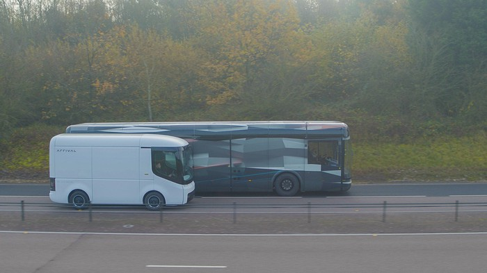 Arrival electric bus and van travel next to each other on a road.
