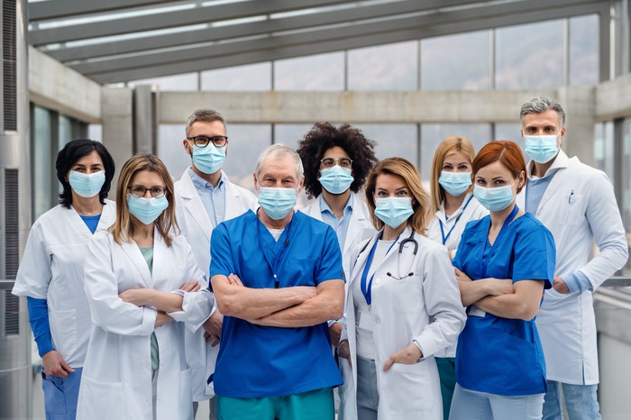 Nine healthcare workers in lab coats and hospital gear wearing masks.
