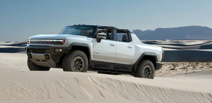A silver GMC Hummer EV, a large electric SUV, on a sand dune.