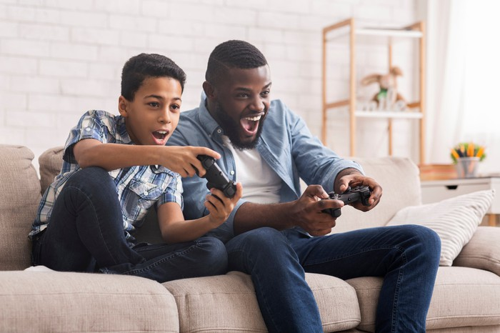 A father and son play a video game together while sitting on a couch.