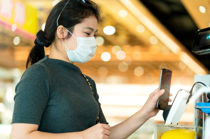 A woman wearing a mask paying for concessions with her phone.