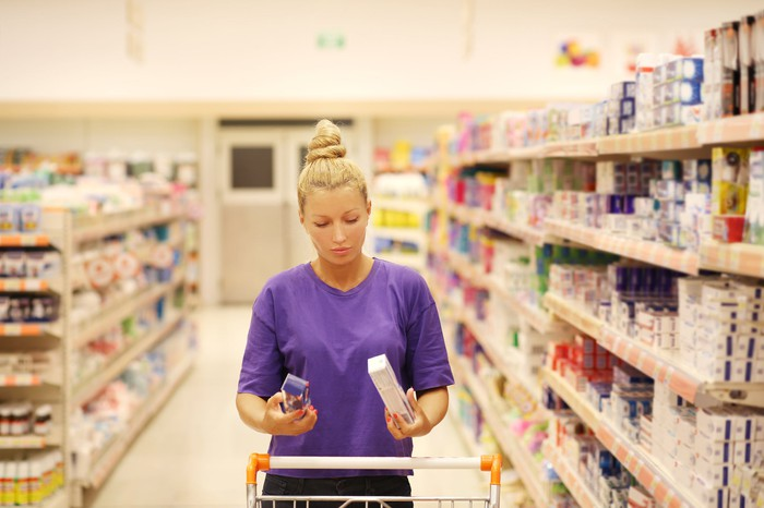 A woman in the aisle of a store holding two toothpaste tubes.