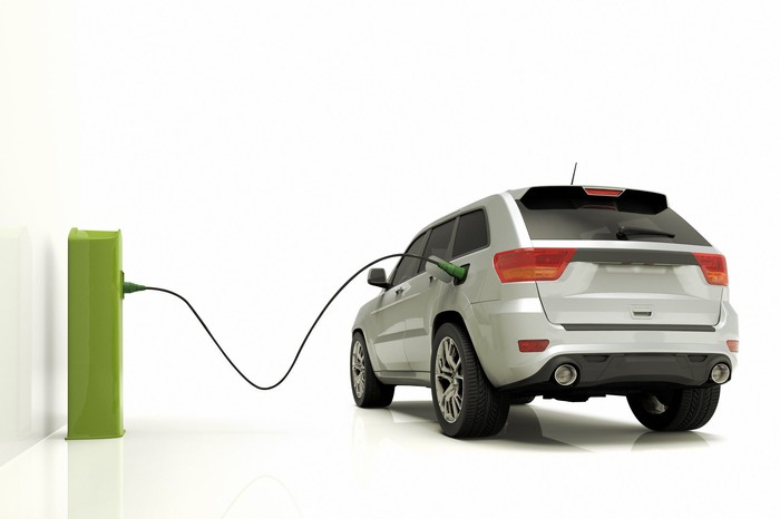 Vehicle plugged into a green charging station.
