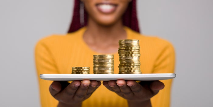 Smiling woman holding plate with increasing stacks of coins