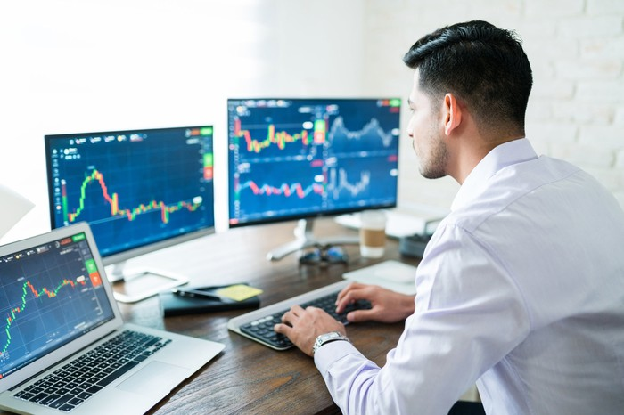 Man looking at stock charts on three computer screens