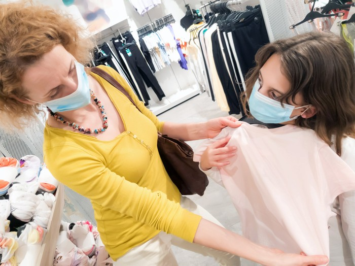 Mother and daughter wearing masks while shopping for children's clothes