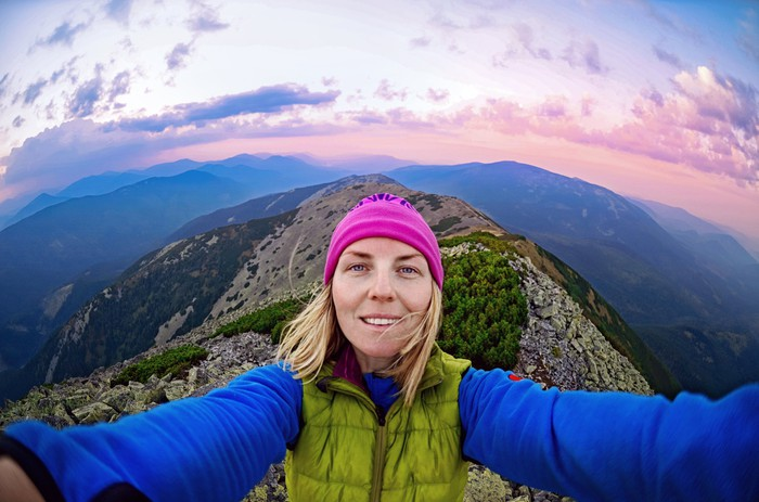 Woman capturing footage of herself on a climb.