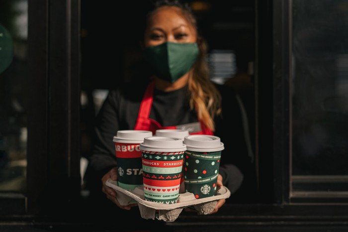 Starbucks employee displaying a tray full of drinks in festive holiday cups.