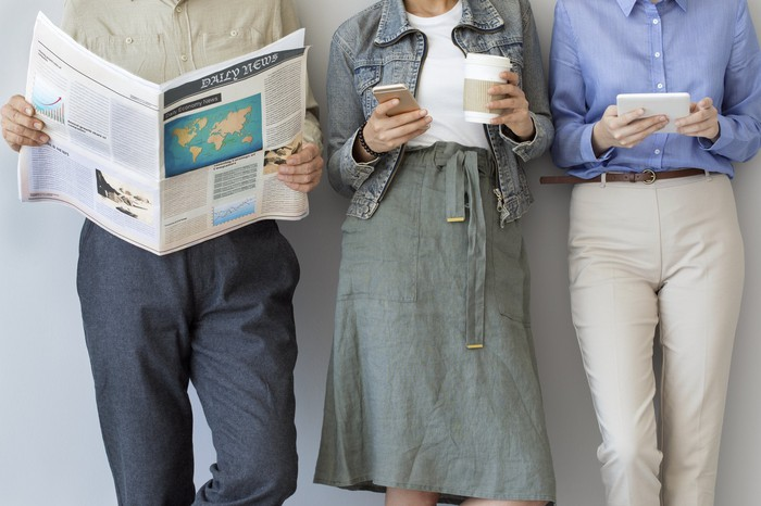 One person reading a newspaper while two others use a phone and tablet.