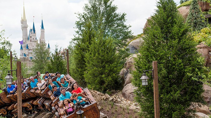 The Seven Dwarfs Mine Ride roller coaster at Disney's Magic Kingdom with the castle in the background.