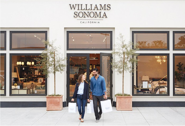A couple walking out of a Williams-Sonoma holding shopping bags