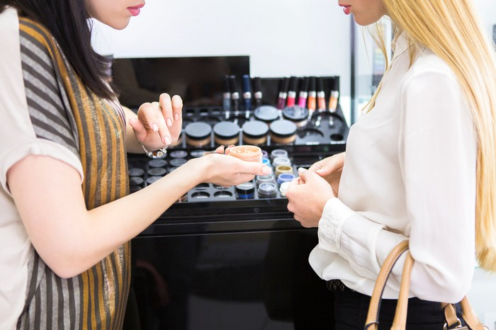 Two women standing at a makeup counter.