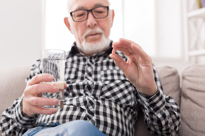 Older man holding water glass in one hand and pill in other