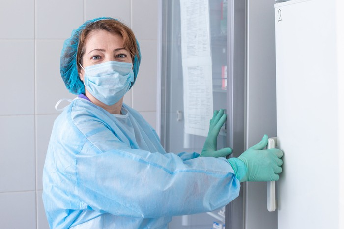 Woman in protective equipment opening a large medical refrigerator