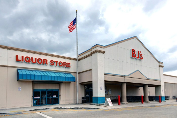 The outside of a BJ's Wholesale store and a liquor store.