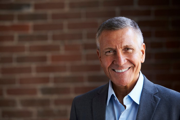 Smiling older person wearing suit in front of brick wall
