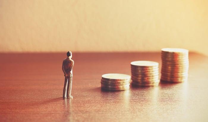 A man facing rising coin stacks