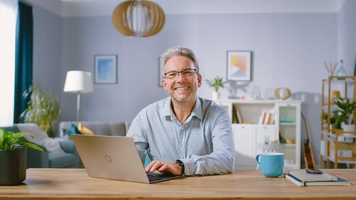 Smiling older person at laptop.