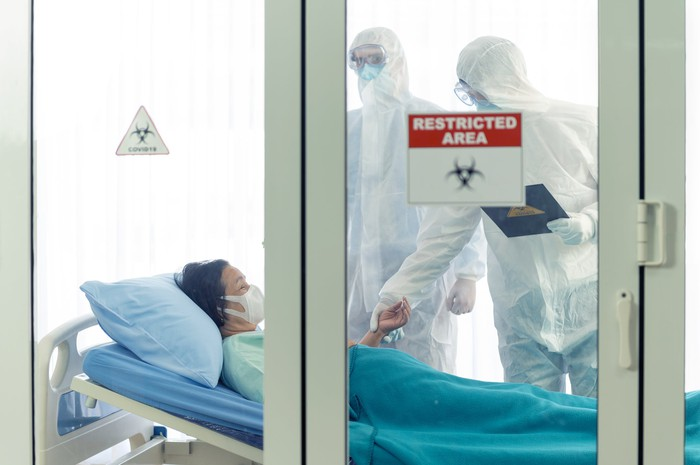 Doctors in protective equipment with a patient behind a restricted area.