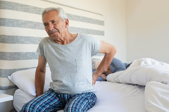 Older person in pajamas sitting up in bed rubbing back.