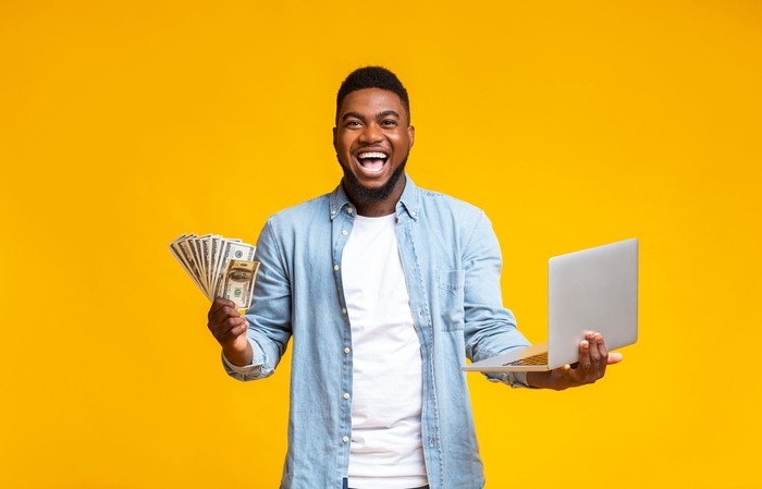 A guy who has a big smile on his face, holding a laptop in one hand and a stack of money in the other.