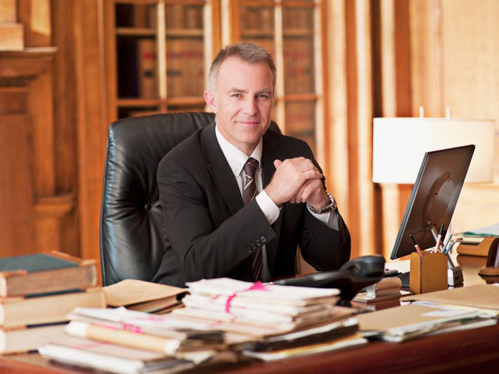 Smiling older person in suit sitting at desk.