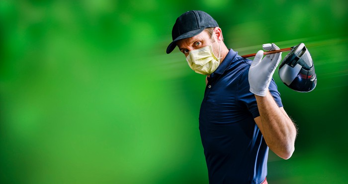 A male golfer  stretches with his driver  behind his head and wears a face mask.