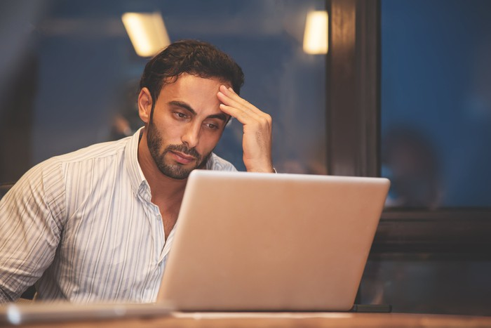 Man holding his head while looking at laptop