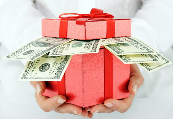 A pair of hands holds a red gift box with hundred-dollar bills poking out.