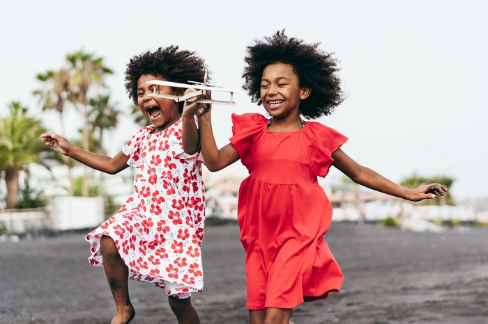 Twin African girls run with glee while holding a wooden airplane.