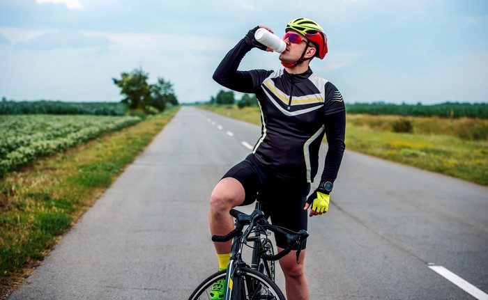 A man riding a bike has stopped on a country  road to drink from his water bottle
