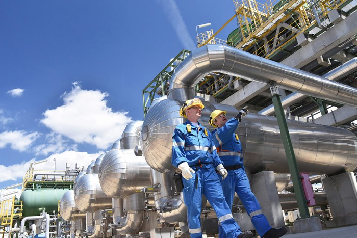 Two workers wearing protective gear in front of oil process equipment at a refinery.