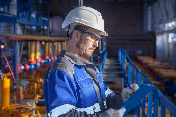 A man inspects oil and gas equipment in a processing facility.