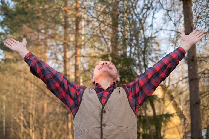 Man outdoors with arms outstretched towards the sky.