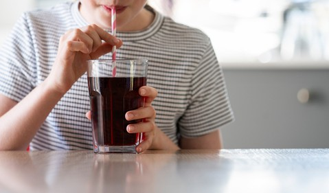 Boy drinking from a glass of cola with a straw
