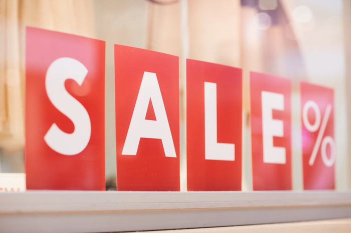 A sign  in white letters against a red background reads the word sale.