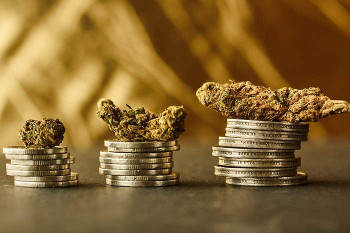 Three ascending stacks of coins each with a marijuana bud on top of it.
