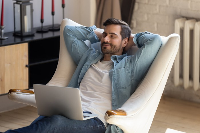 A man relaxing in a padded white lounge chair with a laptop on his lap.