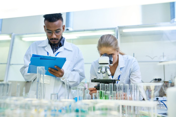 Two scientists working in a lab, with one writing and the other looking through a microscope