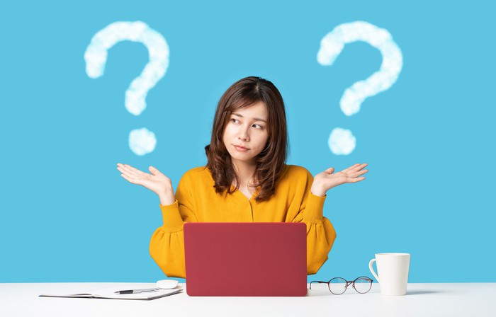 A woman sitting at a table on a laptop looking confused with two question marks above her.