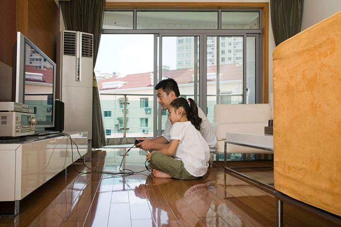 A father and daughter sitting on the floor playing a video game.