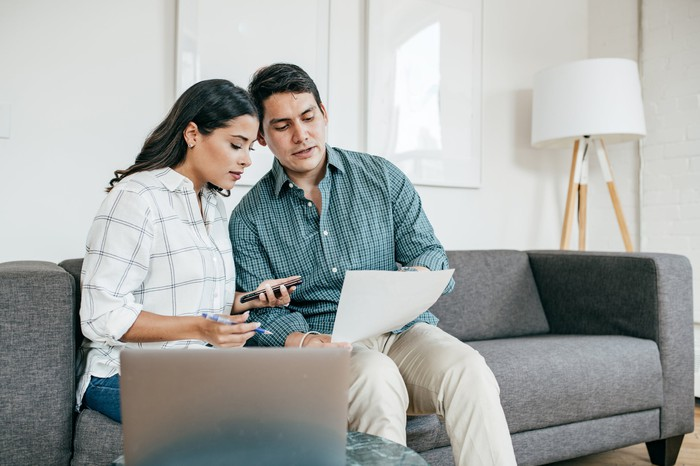 Couple sitting on the couch looking at documents