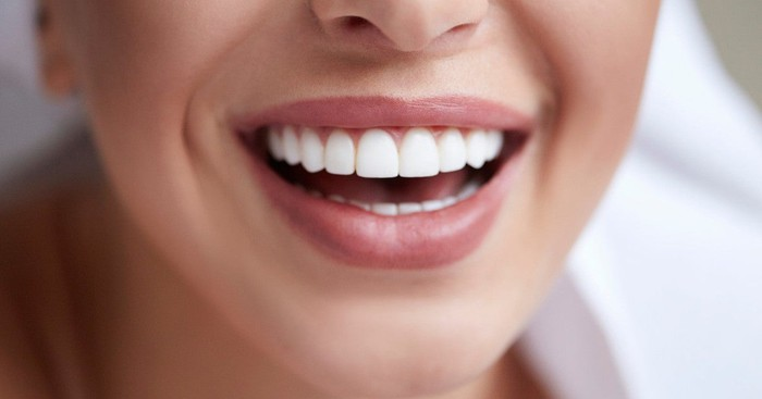 Lower part of a woman's smiling face, showing her nicely aligned front teeth.
