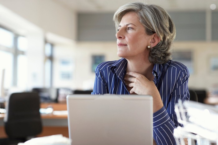 Mature woman sitting in front of a laptop while staring off to the side and thinking.