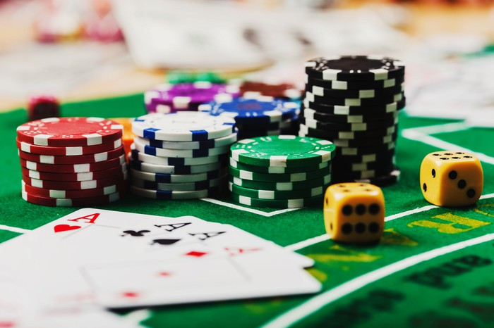 Poker chips, dice and playing cards on a green gaming table.