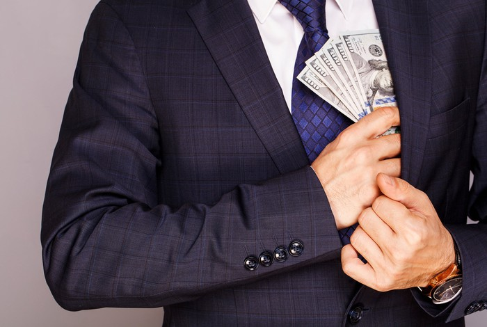 We see the hands of a man putting hundred dollar bills inside his jacket.
