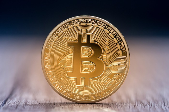 A gold physical bitcoin token standing up on a table.